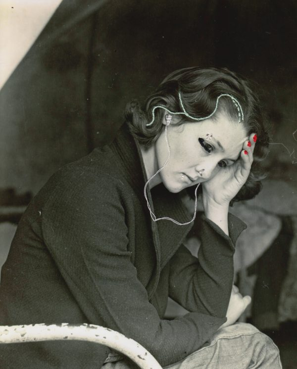 Embroidery art on black and white photo by Dorothea Lange, threaded headphones and facial piercings in woman's ears