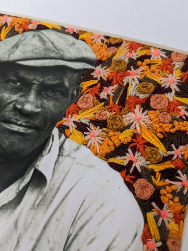 Detail of embroidery art of orange flowers on black and white photo of man sitting on steps